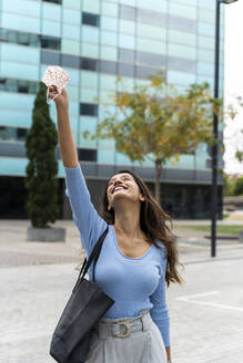 Happy woman with purse holding protective face mask in mid-air against building during COVID-19 - AFVF07555
