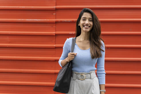Smiling confident woman with purse standing against shutter - AFVF07570