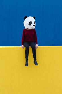 Woman in panda mask sitting on yellow retaining wall - XLGF00777