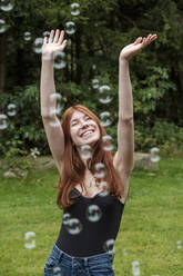 Happy woman with arms raised playing amidst soap bubbles in yard - LBF03261