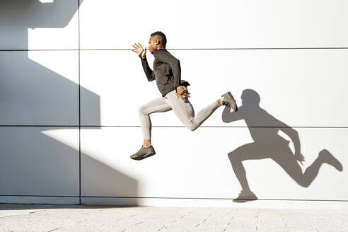 Young athlete running against white wall - GGGF00069
