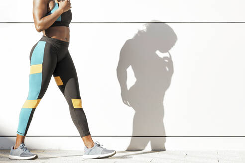 Sportswoman in sports clothing walking against white wall - GGGF00081