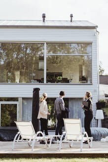 SIde view of real estate agent showing new property to couple - MASF20396