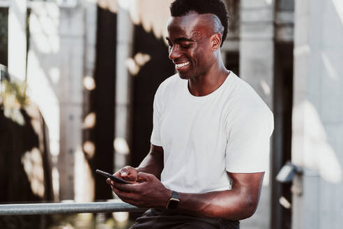 Smiling sportsman text messaging on smart phone sitting - EBBF01356