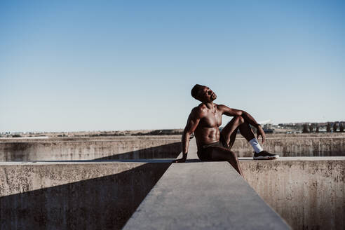 Contemplating male athlete sitting on wall against blue sky - EBBF01377
