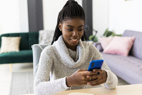 Smiling young woman text messaging on smart phone while sitting in living room at home - GIOF09576