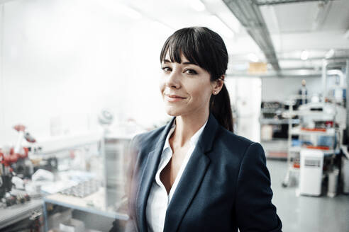 Confident businesswoman smiling while standing at industry - JOSEF02208