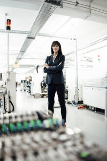 Confident female professional standing with arms crossed at industry - JOSEF02217