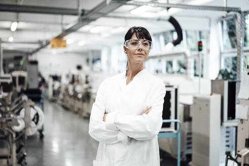 Confident female scientist standing with arms crossed while looking away in bright laboratory - JOSEF02244