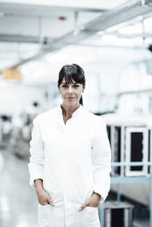 Confident female scientist standing with hands in pockets in bright laboratory - JOSEF02250