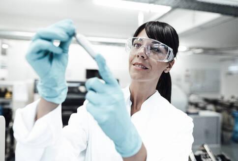 Smiling mature female scientist looking at sample in laboratory - JOSEF02301