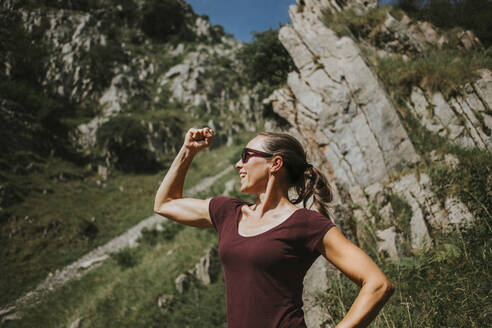 Smiling woman flexing muscles while standing against rock formation on sunny day - DMGF00267