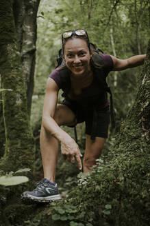 Smiling female trekker bending over by plants in forest - DMGF00288