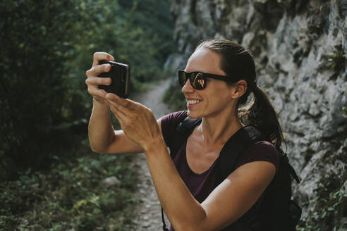 Smiling woman photographing while hiking - DMGF00291