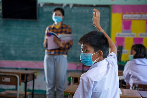 Group of Asian elementary students wearing protective mask to Pr - CAVF90520