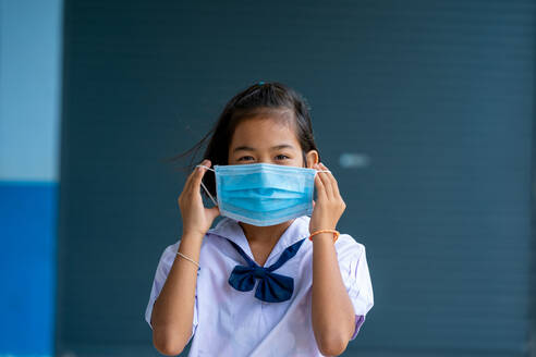 Asian children in school uniform wearing protective mask to Prot - CAVF90523