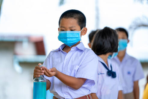 Asian children in school uniform wearing protective mask to Prot - CAVF90526