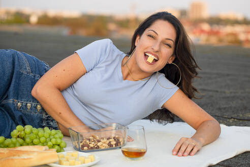 Happy young woman eating cheese while lying on rooftop during picnic - NGF00705