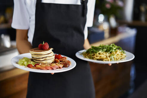 Midsection of female barista holding food plate in coffee shop - BSZF01772
