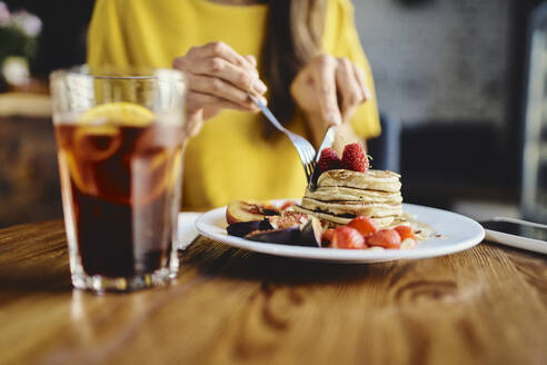 Midsection of young female eating pancake while sitting at table in cafe - BSZF01796