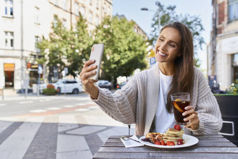 Smiling woman taking selfie through mobile phone while sitting at sidewalk cafe - BSZF01806