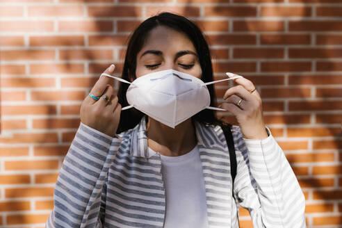 Woman wearing face mask against brick wall - EGAF01010