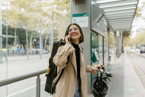 Smiling woman talking on mobile phone while standing at tram station in city - VABF03964