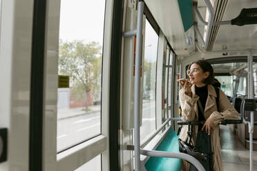 Woman with electric push scooter looking away while talking on mobile phone in tram - VABF03985