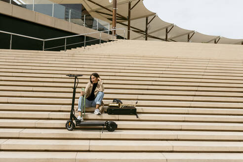 Woman using mobile phone while sitting by saxophone instrument and electric push scooter on staircase - VABF04018