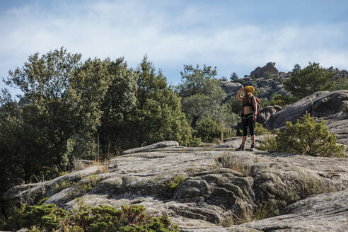 Trekker admiring view while standing on rock mountain at La Pedriza, Madrid, Spain - MRRF00661