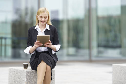 Blond businesswoman using digital tablet while sitting on bench against building - GGGF00083