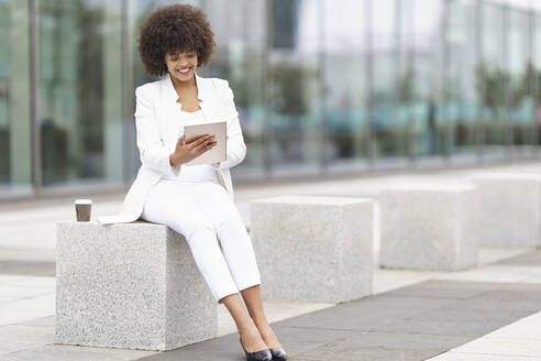 Businesswoman smiling while using digital tablet sitting on bench - GGGF00089