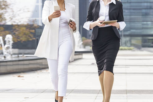 Businesswomen holding with cup using mobile phone and digital tablet while walking on footpath - GGGF00101