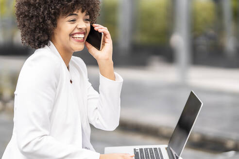Smiling businesswoman talking on mobile phone while sitting on bench outdoors - GGGF00110