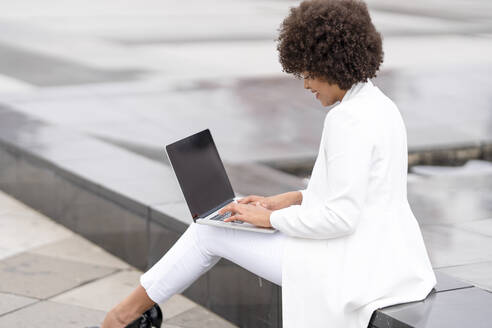 Businesswoman working on laptop while sitting outdoors - GGGF00113