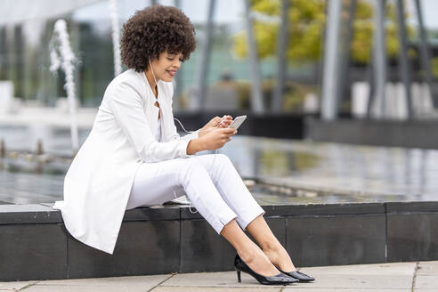 Businesswoman wearing in-ear headphones using mobile phone while sitting on bench outdoors - GGGF00116
