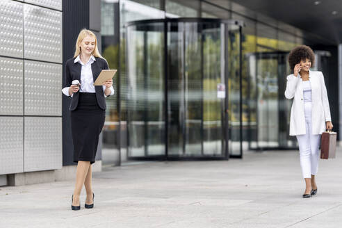 Businesswoman using digital tablet while standing with colleague in background against building - GGGF00128