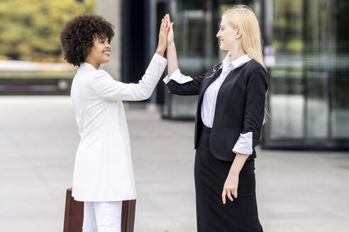 Business people greeting with giving high-five while standing outdoors - GGGF00131