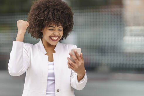Cheerful businesswoman showing winning gesture while using mobile phone outdoors - GGGF00155
