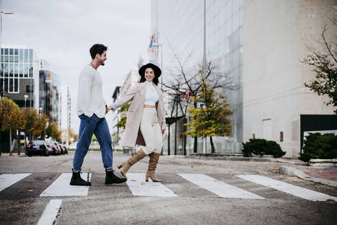 Smiling woman holding hands with male partner while crossing road in city - EBBF01466