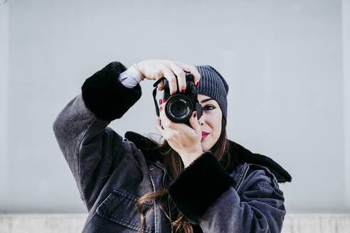Confident woman taking photograph through camera while standing against wall - EBBF01523