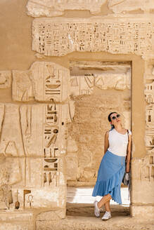 Stylish female traveler standing in between stone construction and admiring historic architecture in ancient ruined heritage building with hieroglyphs on weathered columns - ADSF17315