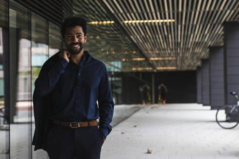 Smiling entrepreneur with hand in pocket holding blazer in city - PNAF00072
