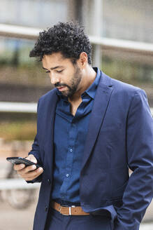 Entrepreneur using mobile phone while standing in city - PNAF00099