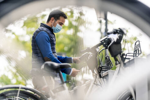 Young man using smart phone at bicycle parking station during COVID-19 - CJMF00362