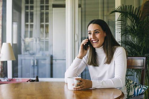 Young woman drinking coffee while talking on mobile phone at home - ABZF03431