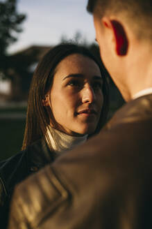 Girlfriend looking at man while standing outdoors during sunset - ABZF03461