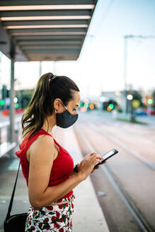 Side view of young female in black protective mask browsing smartphone while standing on railway platform and waiting for train - ADSF17634