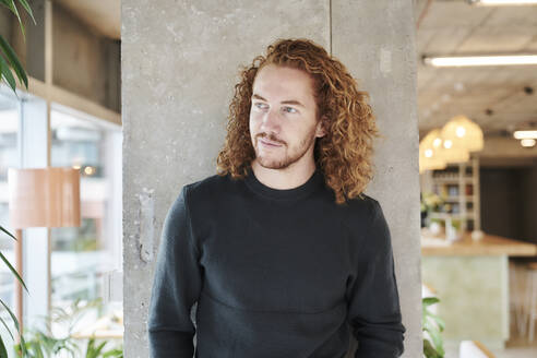 Redhead man looking away while standing against concrete column at home - FMKF06679