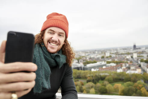 Man smiling while taking selfie through smart phone on building terrace against sky - FMKF06694